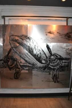 L'une des toiles de Pierre Routhier, faite sur des feuilles d'aluminium, nous donne presque l'impression quecelle-ci est une partie de la carlingue d'un avion. Un autre clin d'oeil à la thématique «internationale». ()