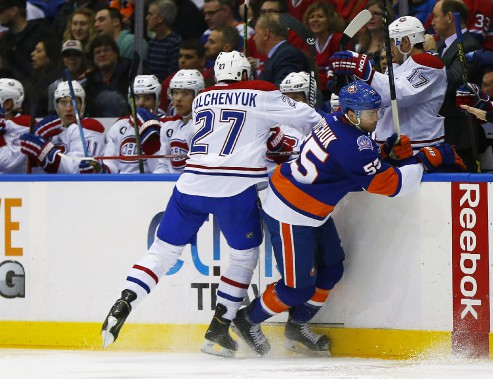 L'attaquant du Canadien Alex Galchenyuk met en échec Johnny Boychuk près du banc de son équipe. (Photo Andy Marlin, USA Today)