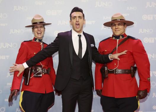 L'animateur de la soirée JacobHoggard accompagné de la police montée. (La Presse Canadienne)