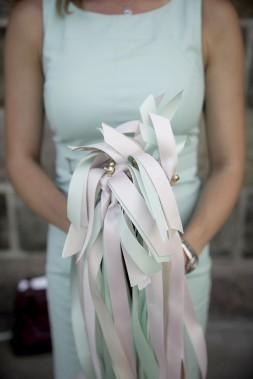 Les tiges à rubans pastel remises aux invités pour être agitées à la sortie de la célébration sont du plus bel effet en photo. (Photo de Jonathan Robert (Emmanuelle Poirier Mariages & Événements))