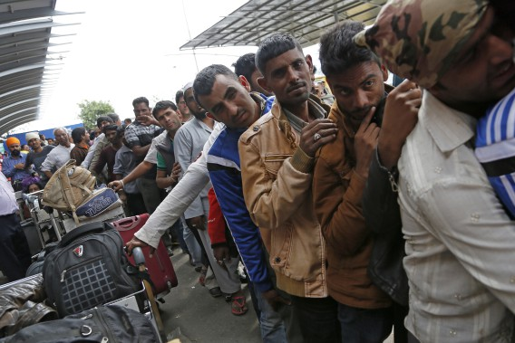 Des Indiens attendent en file avant de pouvoir quitter le pays. (Associated Press)