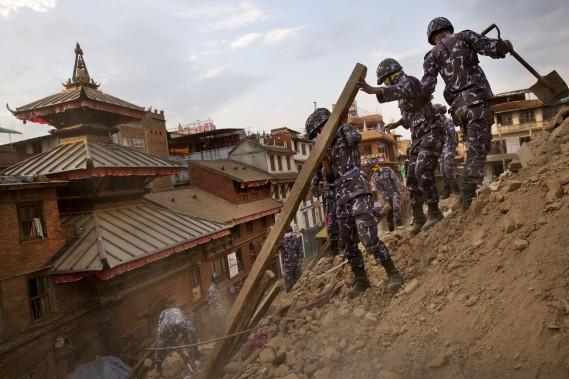 Des policiers népalais nettoient les débris. (Associated Press)