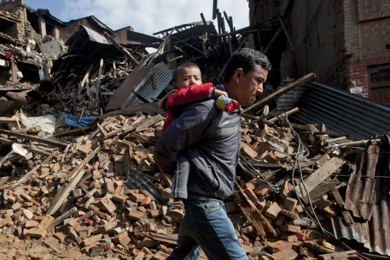 Transportant un enfant sur son dos, cet homme passe devant un immeuble réduit à l'état de gravats, à Bhaktapur, en banlieue de Katmandou., le 27 avril. (PHOTO Niranjan Shrestha, AP)