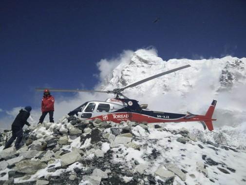 À l'aide de leur hélicoptère, des secouristes se préparent à évacuer des alpinistes pris au camp de base sur le versant népalais de l'Everest, le 27 avril. (PHOTO Azim Afif, AP)