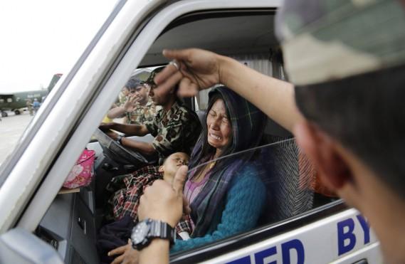 Une femme à bord d'une ambulance, son enfant blessé dans les bras, fond en larmes, alors qu'elle est évacuée vers l'aéroport de Katmandou, le 27 avril. (PHOTO Altaf Qadri, AP)