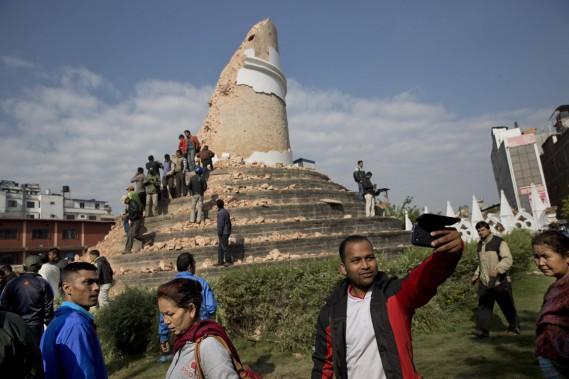 Un touriste prend un égoportrait devant les restes de la tour historique de Dharahara qui s'est effondrée lors du séisme.   (PHOTO Bernat Armangue, AP)