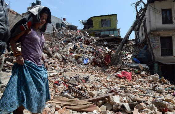 Une femme passe devant une maison ravagée par le séisme, à Katmandou, le 27 avril. (PHOTO PRAKASH SINGH, AFP)