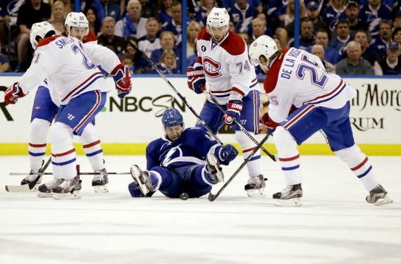 Tyler Johnson trébuche alors qu'il est entouré par plusieurs joueurs du Canadien. (Photo Wilfredo Lee, AP)