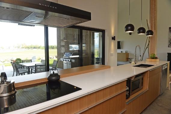 Des armoires de pin blanc et un comptoir de quartz très mince composent une cuisine vaste et fonctionnelle. ()