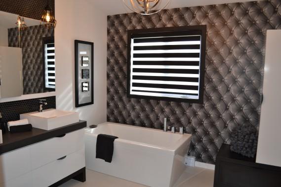 La salle de bains du rez-de-chaussée a des allures romantique avec son papier-peint à effet capitonné et son décor dans des tons de blancs, de noirs et de gris. ()