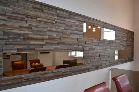 Dans la salle à manger, une portion de mur est recouverte de lamelles de bois avec insertion de miroirs et effet trois dimensions. ()