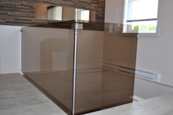 La rampe d'escalier est une réalisation de Vitrerie Boily. Il s'agit d'une pièce de verre trempé fumé de couleur bronze. ()