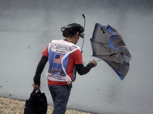 Un travailleurs de piste en découd avec son parapluie après l'annulation des qualifications. (Photo AP, Eric Guay)