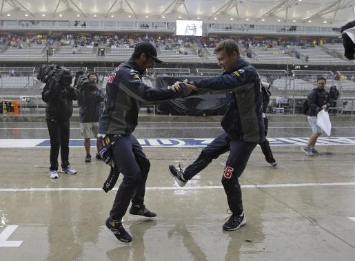 Pourquoi ne pas danser sous la pluie? Les pilotes Daniel Ricciardo et Daniil Kvyatne (Red Bull) ne s'en privent pas. (AFP, Darron Cummings)