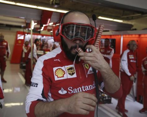 Un employé de l'écurie Ferrari craint le pire en revêtant son masque de plongée artisanal. (AFP, Darron Cummings)