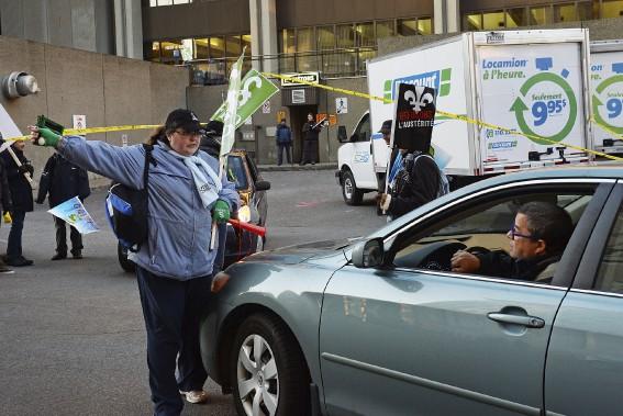 Une syndiquée indique à un automobiliste que l'accès à son stationnement est bloqué, en raison de la grève sur la colline parlementaire. (Le Soleil, Patrice Laroche)