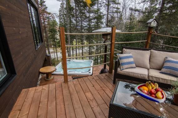 La vaste terrasse en bois accueille un spa en plus d'un coin détente. (Courtoisie Édith Harvey)