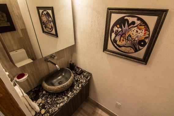 À la salle d'eau le lavabo est sculpté dans la roche et déposé sur un comptoir de granit en roches de rivière. (Courtoisie Édith Harvey)