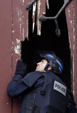 Un policier regarde à l'intérieur de l'Église Neuve, dont la porte vient d'être défoncée par ses collègues. (PHOTO KENZO TRIBOUILLARD, AFP)