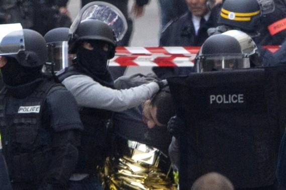 Un homme est arrêté à l'issue d'un raid mené par les forces de l'ordre françaises à Saint-Denis, banlieue proche située au nord de Paris. (PHOTO PETER DEJONG, AP)