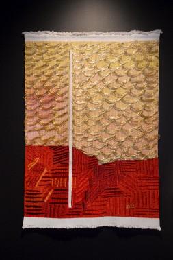 Décédée en 2009, Micheline Beauchemin est une figure marquante de l'art textile québécois. Cette tapisserie de haute lice évoque un paysage symbolique de Grondines, son lieu de résidence. Les fibres rouges représentent la terre, et les jeux de fibres brillantes, le fleuve reflétant les rayons du soleil. (Le Soleil, Jean-Marie Villeneuve)
