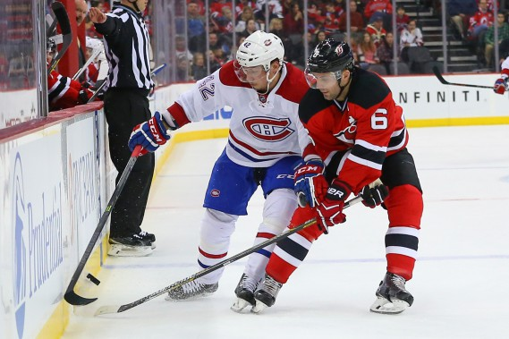Sven Andrighetto et Andy Greene se battent près de la bande pour le contrôle de la rondelle. (PHOTO ED MULHOLLAND, USA TODAY)