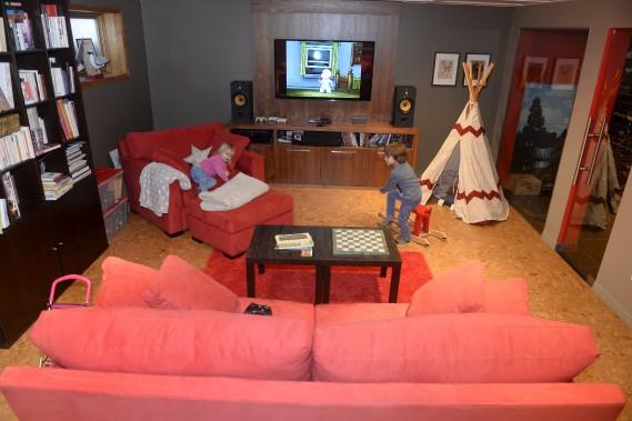 Au sous-sol, la salle familiale prend des tons de rouge et de gris. Le plancher de liège a conquis les propriétaires pour trois raisons. Il est écologique, confortable et chaud. (Le Soleil, Jean-Marie Villeneuve)