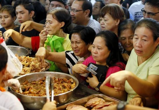 Des Philippins se massent dans les marchés d'alimentation de Manille le 24 décembre pour effectuer leurs achats de dernière minute avant le réveillon de Noël. (AP, Bullit Marquez)