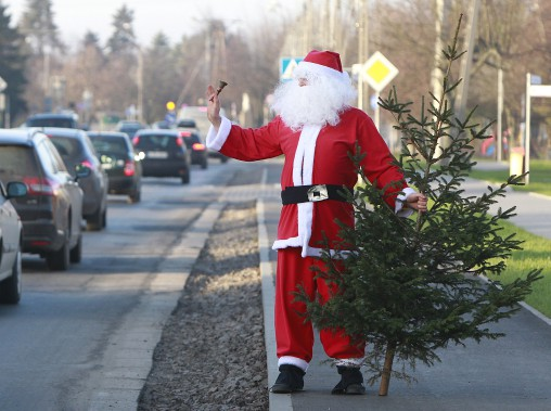 Un homme déguisé en père Noël vend des sapins la veille de Noël à Lomianki, en Pologne. (AP, Czarek Sokolowski)