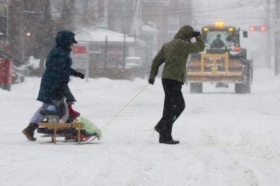 Ces jeunes parents ont troqué la poussette pour le traîneau afin de se déplacer dans la tempête, mardi, ici au coin des rues Royale et Bonaventure à Trois-Rivières. (Sylvain Mayer)