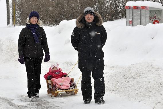 Guillaume et Audrey Simard se baladaient dans les rues enneigées de Kénogami, samedi, avec leur petite Alice, âgée de 15 mois. C'était une journée parfaite pour les promenades en traîneau. (Photo Le Progrès-Dimanche, Rocket Lavoie)