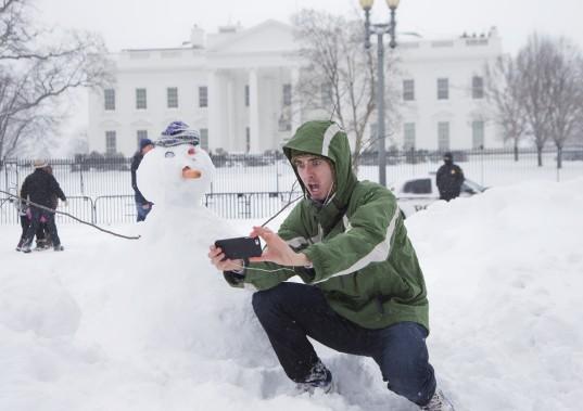 Un touriste prend un selfie avec un bonhomme de neige devant la Maison-Blanche. Washington a été ensevelie sous trois pieds de neige, la circulation était impossible pour les voitures. (Associated Press)