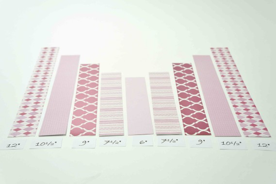 Étape 2.Tailler les bandes sur la longueur pour en obtenir deux de 30,4cm (12po), deux bandes de 26,6cm (10,5po), deux bandes de 23cm (9po), deux bandes de 19cm (7,5po) et une bande de 15,2cm (6po) pour le centre (papier uni ou motifs recto verso). Étape 3.Superposer les bandes, en mettant la plus courte au centre (6 pouces) et en ajoutant de part et d'autre en ordre croissant celles de 7,5... (Fournie par Michaels)