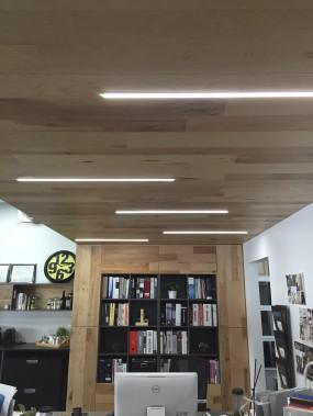Des DEL ont été intégrés dans des profilés en aluminium encastrés dans une retombée de plafond en bois. Il s'agit des nouveaux bureaux de Loca Design, sur le boulevard Hamel, à Québec. ()
