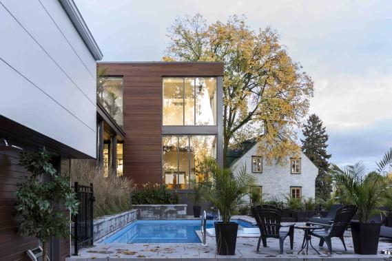 Vue de l'arrière en été. Un bel exemple de cohabitation entre une maison contemporaine et une autre patrimoniale. (CCM2 architectes, Dave Tremblay)