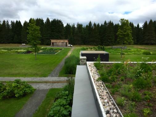 Au premier plan, on aperçoit une partie du toit végétalisé, ainsi que l'extrémité du long mur en pierre locale qui protège la cour des vents violents. Plus loin, on voit les jardins de La Bergerie consacrés à la production maraîchère. (PHOTO FOURNIE PAR L'OEUF)