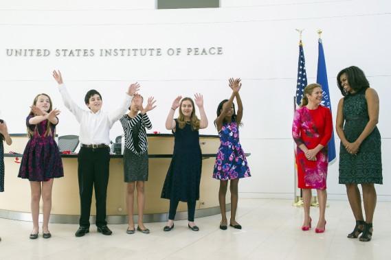 Sophie Grégoire-Trudeau et Michelle Obama observent des élèves qui chantent une chanson à l'Institut de la Paix. (AP, Cliff Owen)