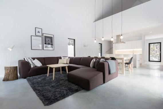 Le salon, la salle à manger et la cuisine sont rassemblés dans un vaste espace ouvert au rez-de-chaussée, avec plancher de béton. Les grandes ouvertures ainsi que la double hauteur de plafond assurent une grande luminosité. (Photo Dave Tremblay, fournie par Cargo architecture)
