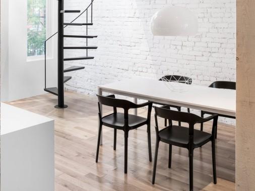 Dépouillée et lumineuse, la salle à manger est meublée de chaises noires faites de bois et d'acier (chaise Steelwood, dessinée par les frères Bouroullec), qui font écho à l'acier noir de l'escalier. Une suspension lustrée se fond dans l'environnement dominé par le blanc. (PHOTO ADRIEN WILLIAMS, FOURNIE PAR ANNE SOPHIE GONEAU DESIGN)