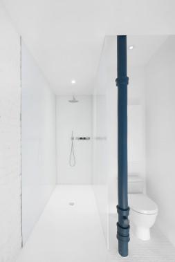 Résolument minimaliste, la salle de bains immaculée contient une longue douche aux parois de verre dont l'endos est blanc. Une résine d'époxy recouvre le sol de la douche. «L'idée était de multiplier les réflexions par les surfaces brillantes», précise Anne Sophie Goneau. Plutôt que d'être camouflé, l'ancien tuyau de fonte peint en bleu-vert ponctue l'espace. «J'ai choisi cette couleur, car elle s'harmonise aux reflets bleutés du vitrage», justifie-t-elle. (PHOTO ADRIEN WILLIAMS, FOURNIE PAR ANNE SOPHIE GONEAU DESIGN)