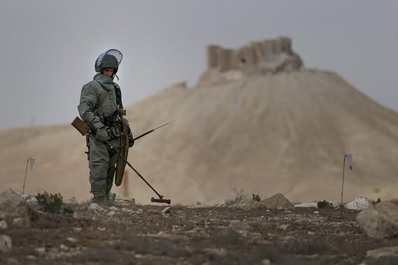 Protégés par une épaisse combinaison et munis de détecteurs, les militaires russes balaient les monticules de sable qui entourent le site archéologique à la recherche de mines et d'explosifs laissés par les combattants de l'EI avant leur fuite. (AFP, fournie par le ministère russe de la Défense)