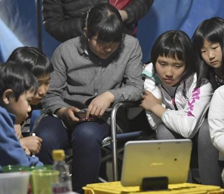 De jeunes sinistrés regardent les nouvelles dans le refuge d'une école du village de Nishihara. (AP, Yohei Nishimura)