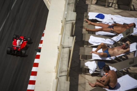 Des Monégasques en maillot de bain semblent faire peu de cas du passage de Kimi Raikkonen (Ferrari) dans les rues de Monaco. (AFP, ANDREJ ISAKOVIC)
