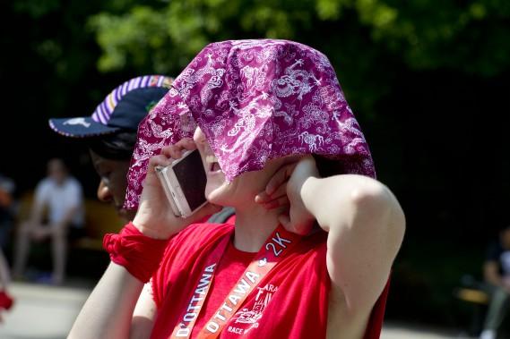 Jennifer O'Maley se protège du soleil après sa course de 5 km, samedi. (Martin Roy, LeDroit)