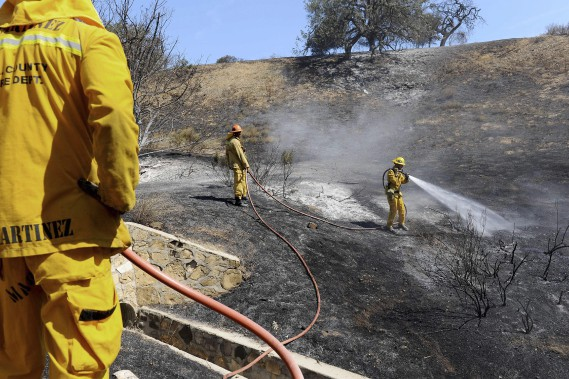 La végétation très asséchée de la région a aidé le feu à se propager. Les pompiers ont travaillé toute la journée dimanche afin d'éviter la propagation du brasier. (AFP, Michael Owen Baker)