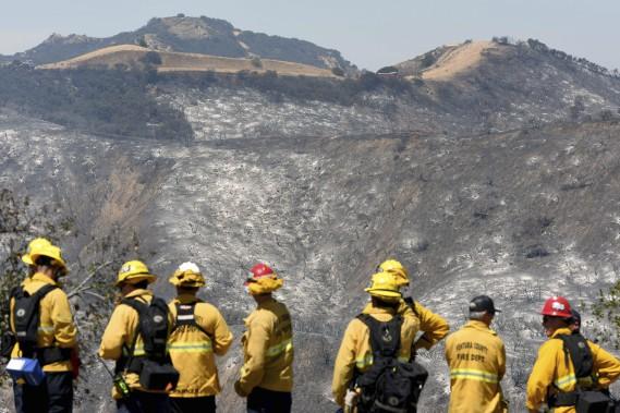 Des pompiers observent la vallée incendiée de Calabasas, en Californie. (AFP, Michael Owen Baker)