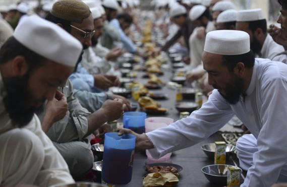 En groupe, ces pratiquants préparent une repas communautaire. (AFP)