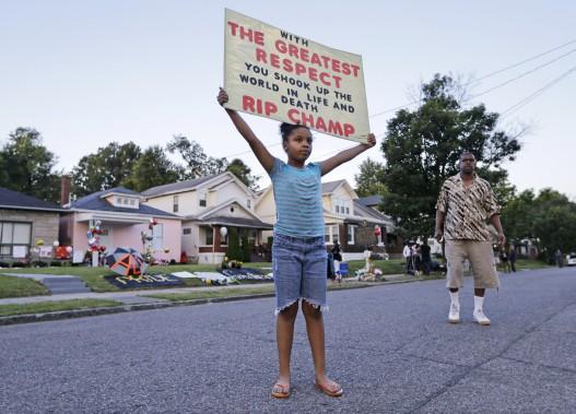 Akera Price-King, 9 ans, tient une pancarte devant la première maison d'Ali, à Louisville, avant la procession funéraire. (AP)