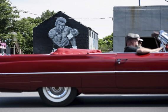 Un voiture passe devant une murale rappelant la victoire d'Ali contre Sonny Liston en 1965, dans la ville natale du champion. (AFP)
