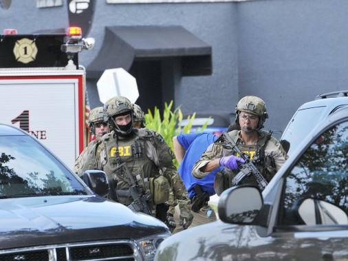 Le FBI, de même que la police départementale d'Orlando et le personnel du bureau du shériff d'Orange County, menaient leur enquête sur les lieux de la tragédie, dimanche. (AP, Craig Rubadoux)